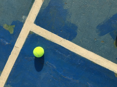 surface: Old tennis court lines, color, ball on the daytime.