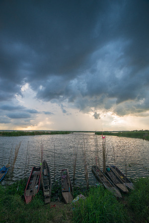 The beautiful sky with the fisherman's boats yard that were docked at the lakeside and the rural scene.