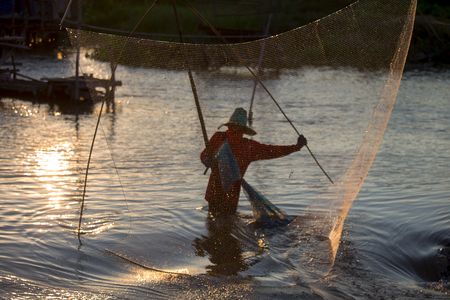 fishing scene: The Asian fisherman�s fishing at the lake by his equipment with rural scene. Stock Photo