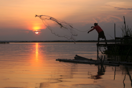 The Asian fisherman's fishing at the lake by his equipment with rural scene.