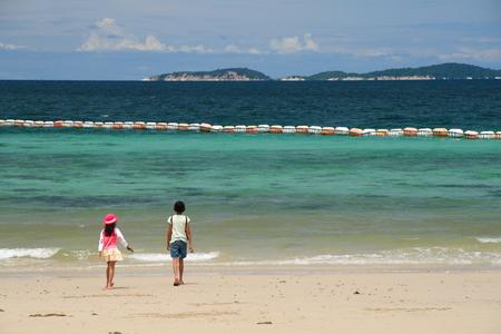 Two girls walking along the beach