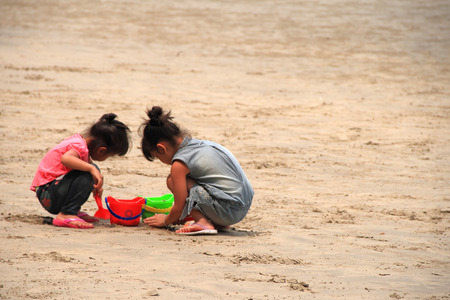 children sandcastle: two girls playing with sand on the beach
