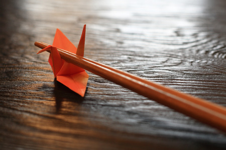 crane origami: Origami paper crane chopsticks rest on wooden table