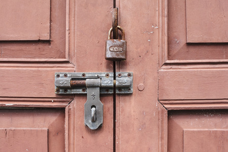 iron barred: Rusty lock and bolts on red wooden door Stock Photo
