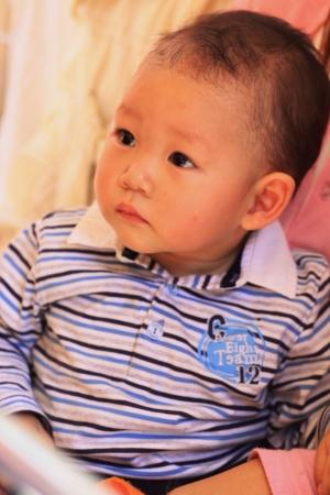 eye: Asian baby boy in motherarms looking forward. Stock Photo