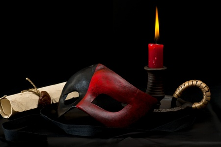 black mask: Carnival mask with candle and old scroll on the dark Stock Photo