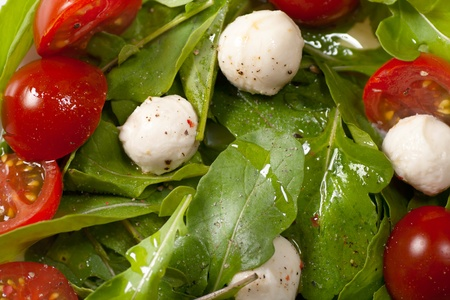 Salad with mozzarella and arugula background