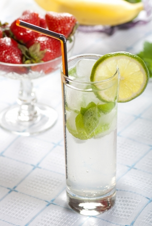 Mohito with lime and basil leaves