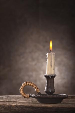 Burning candle on dark background photo
