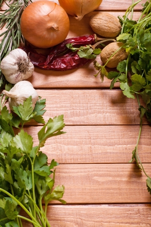 Various herbs with onion, garlic and walnut background