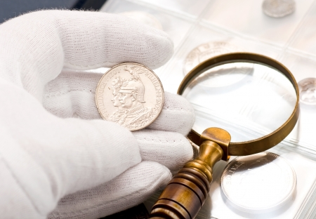 오래 된 은색 동전과 돋보기