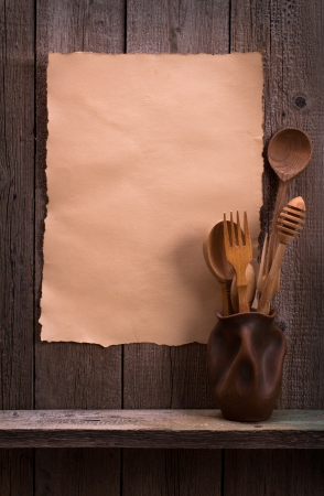 Cutlery set and old paper on wooden wall photo