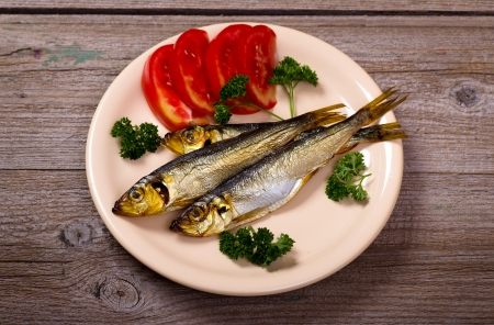 sprat: Smoked fish with tomatoes on plate top view Stock Photo