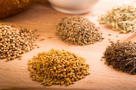 fenugreek: Whole spice piles including dried fenugreek, coriander and caraway