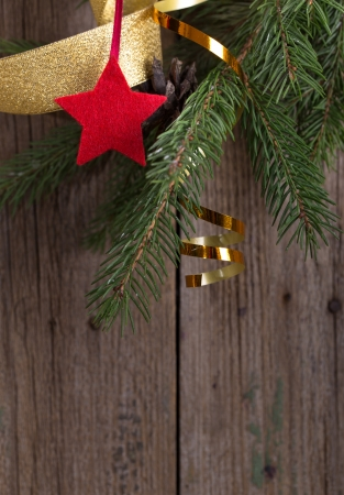 Christmas decoration with fir branches and star on old  wooden background photo