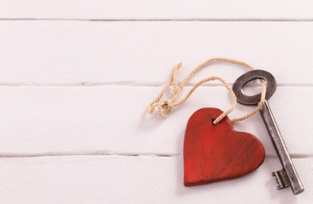 Old  key with a heart on white wooden  Standard-Bild