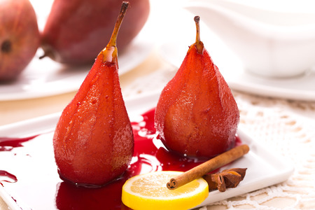 Two poached pears in red wine with cinnamon Stock Photo
