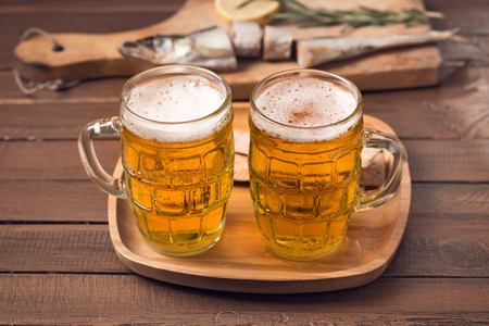 Two mugs of beer on wooden table photo