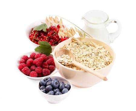 Bowls of oat flakes cereal and various berries and milk isolated on white photo