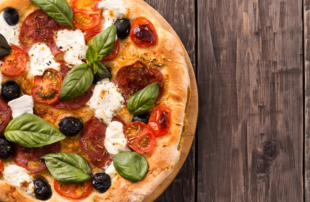 Pizza with salami, mozzarella, olives and basil top view with copy space rustic style