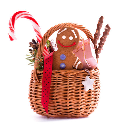 Christmas gift basket with treats and gingerbread man isolated on white photo