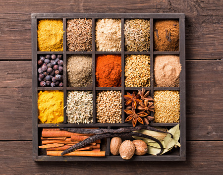 Various herbs and powder spices in box on old wooden background top view