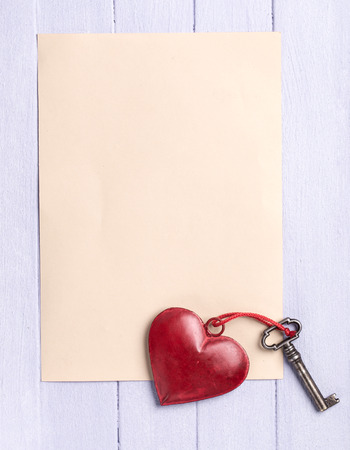 Empty sheet of paper on painted wooden background with a vintage heart and old key photo