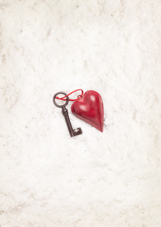 Vintage heart decoration and old key at center of white snow background. Concept of Valentines day. photo