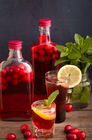 alcoholic beverage: Shots and bottles of artisan cranberry alcoholic beverage