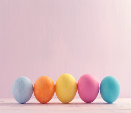 backdrop colorful: Five multicolored Easter eggs on wooden painted background Stock Photo