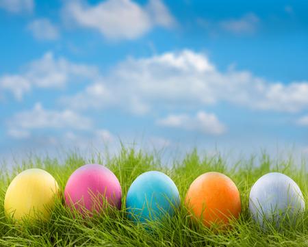 푸른 하늘 배경에 잔디에 장식 된 부활절 달걀의 행
