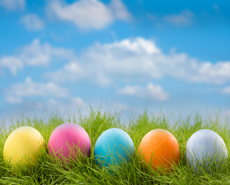 Row of decorated easter eggs in grass on blue sky background Standard-Bild