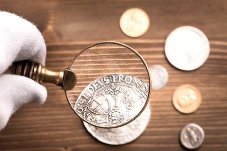 나무 테이블에 돋보기를 통해 골동품 은색 동전을 검사
