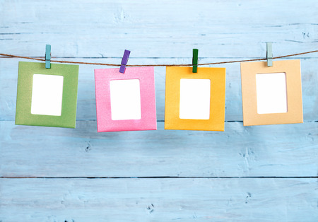 Four colored paper photo frames hanging on rope on blue painted background