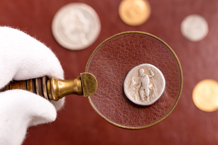Examining antique Roman silver coin through magnifying glass on red leather surface Stock Photo