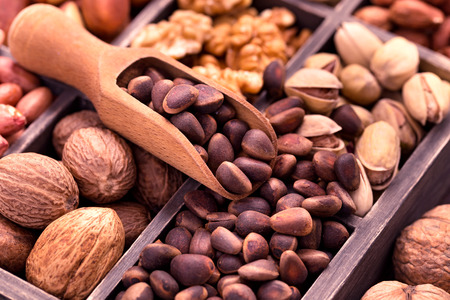 pine nuts: Pine nuts in scoop and other nuts in box closeup Stock Photo