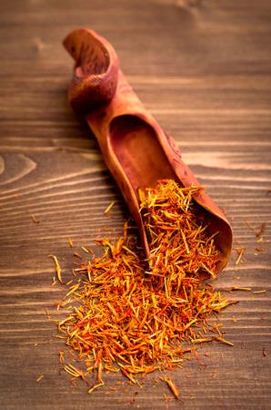 Saffron spice threads in oriental sandalwood handcraft scoop on wooden background closeup