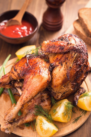 roast chicken: Grilled chicken with sauce and tomatoes on wooden plate