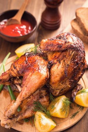 pollo asado: Pollo a la parrilla con salsa y los tomates en la placa de madera