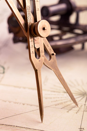 Brass proportional divider on old map closeup shot
