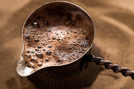 cezve: Coffee brewing in turkish pot in hot sand, cezve. Closeup shot, top view.
