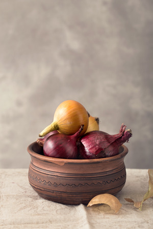 red onions: Rustic bowl of yellow and red onions