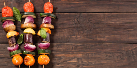 Grilled veggie skewers at left side old rustic wooden background with copy space Standard-Bild