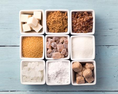 Bowls of various kinds of sugar on old blue background