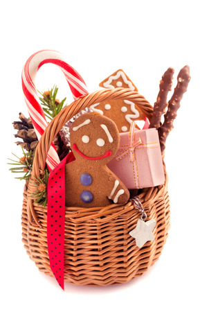 Gingerbreadman and other treats into Christmas gift basket on white