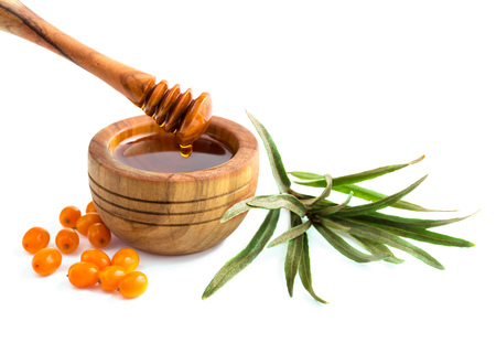 Small bowl of sea buckthorn oil isolated on white