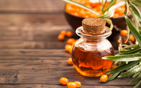 Sea buckthorn oil and branch with berries at right side of wooden background