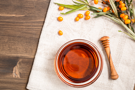 Sea buckthorn oil and branch with berries at right side top view Stock Photo