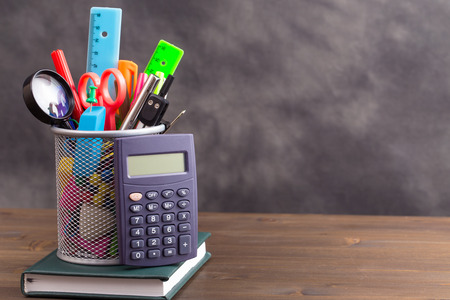 crayon  scissors: Stationery items with calculator at left side on wooden table on gray background