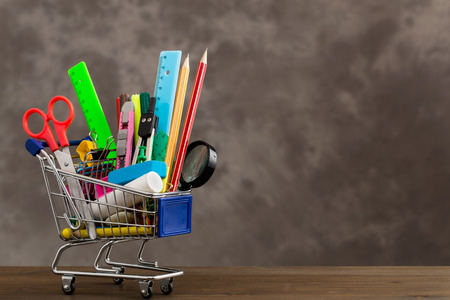 stationery items: Stationery items in shopping trolley at left side of table on gray background Stock Photo